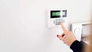 Young woman entering security code on home security alarm system keypad
