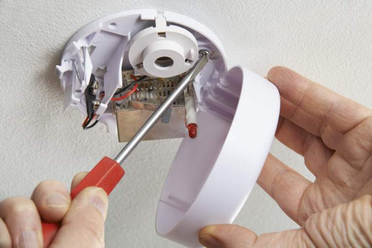 Close Up Of Installing Smoke Detector At Home